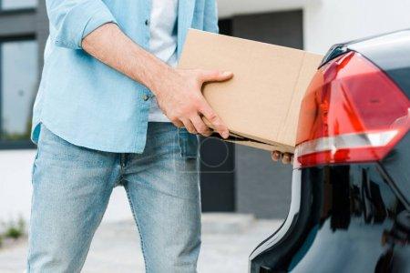 Photo pour Vue recadrée de l'homme mettant boîte en carton dans la voiture moderne - image libre de droit
