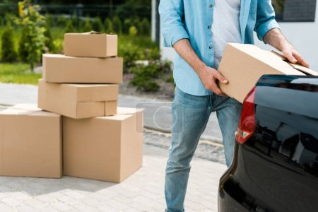 cropped view of man standing near car while putting box