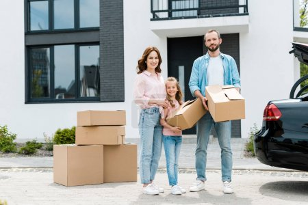 Photo for Cheerful family standing with boxes while moving into modern house - Royalty Free Image