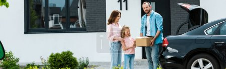 panoramic shot of cheerful family moving into modern house while standing near car