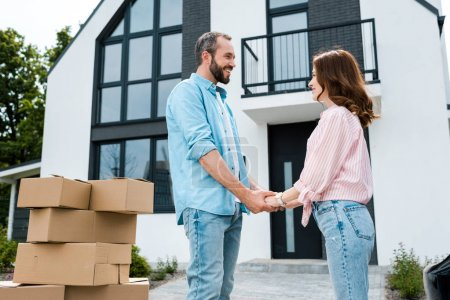 Photo for Happy woman holding hands with bearded man near boxes and new house - Royalty Free Image