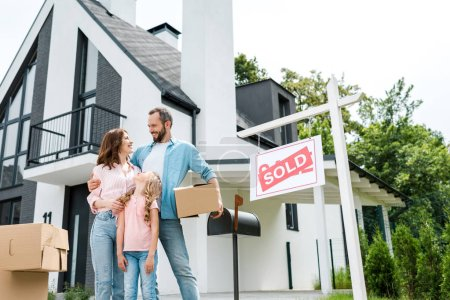 bearded man holding box and standing with wife and daughter near house and board with sold letters