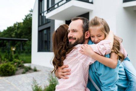Photo pour Homme barbu gai et heureux enfant câlin avec femme près de la maison - image libre de droit