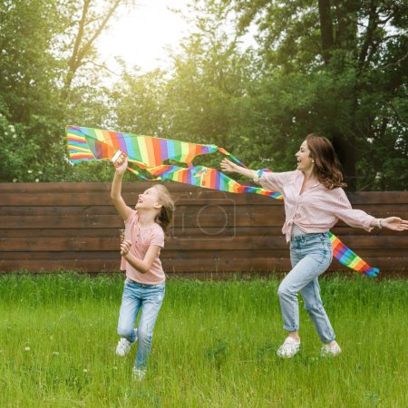 Photo for Happy mother with outstretched hands near cute kid with colorful kite - Royalty Free Image