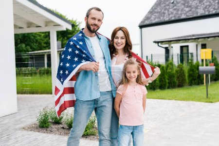 happy family standing with american flag near house