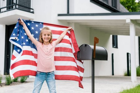 Photo for Happy kid standing and holding american flag near mail box and house - Royalty Free Image