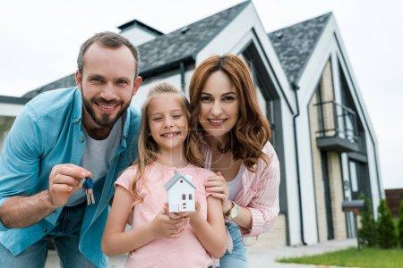 fröhliches Kind mit Papphausmodell in der Nähe von Vater mit Schlüssel und glücklicher Mutter