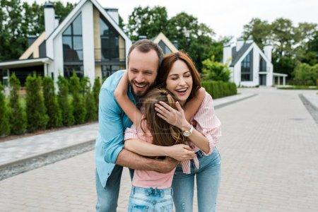 Photo pour Vue arrière de l'enfant étreignant les parents heureux sur la rue - image libre de droit