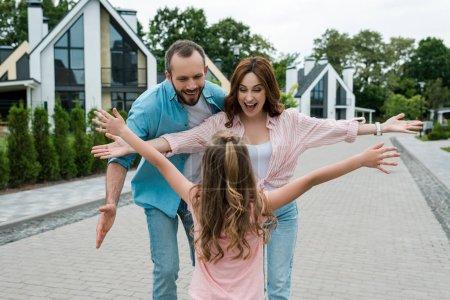 Foto de Vista trasera del niño con las manos extendidas de pie cerca de los padres felices - Imagen libre de derechos