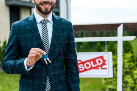 Photo for Cropped view of cheerful broker holding keys near board with sold letters - Royalty Free Image