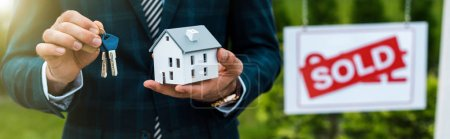 panoramic shot of realtor holding carton house model and keys near board with sold letters