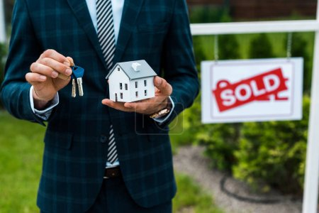 Photo pour Cropped view of realtor holding carton house model and keys near board with sold letters - image libre de droit