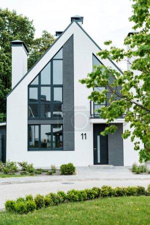 Photo pour Foyer sélectif de l'herbe verte près de la nouvelle maison moderne et de luxe - image libre de droit