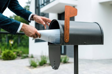Photo pour Cropped view of man putting blank paper in mail box near house - image libre de droit