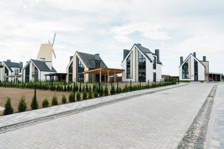 Photo pour Rue avec de nouvelles maisons modernes et de luxe près des plantes vertes et des arbres - image libre de droit