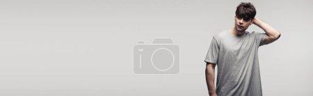 Photo pour Tir panoramique de la main réfléchie de fixation d'homme derrière la tête d'isolement sur le concept gris, d'émotion humaine et d'expression - image libre de droit