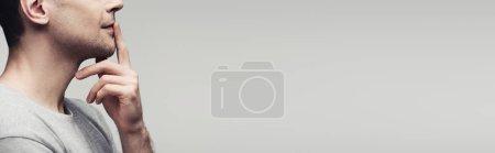 Photo pour Vue recadrée de l'homme muet affichant le signe silencieux d'isolement sur le fond gris, projectile panoramique, concept humain d'émotion et d'expression - image libre de droit