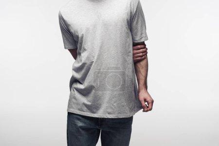 Photo pour Vue partielle de l'homme dans le t-shirt gris retenant la main derrière le dos isolé sur le concept gris, humain d'émotion et d'expression - image libre de droit