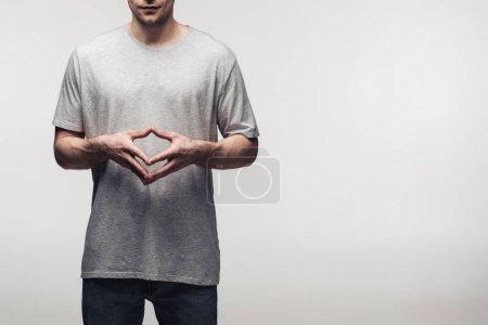 Photo pour Vue partielle de l'homme dans le t-shirt gris affichant le geste de clocher tout en utilisant le langage corporel isolé sur le concept gris, d'émotion humaine et d'expression - image libre de droit