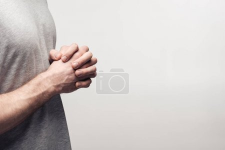 Photo for Partial view of man holding clenched hands isolated on grey, human emotion and expression concept - Royalty Free Image