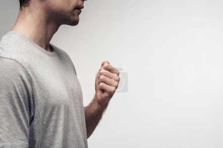 Photo for Partial view of man holding fist while using body language isolated on grey, human emotion and expression concept - Royalty Free Image