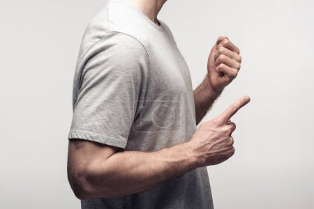 Foto de Partial view of man holding fist and pointing with finger isolated on grey, human emotion and expression concept - Imagen libre de derechos
