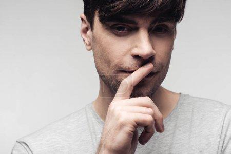 Photo pour Homme muet pensif affichant le geste de silence d'isolement sur le concept gris, d'émotion humaine et d'expression - image libre de droit