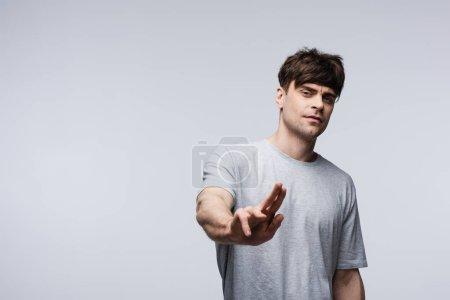 Photo pour Homme mécontent affichant le geste d'arrêt d'isolement sur le concept gris, d'émotion humaine et d'expression - image libre de droit
