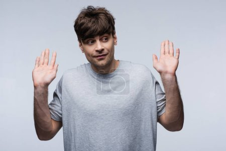 smiling man showing give up gesture and looking away isolated on grey, human emotion and expression concept
