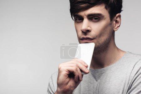 Photo pour Cher homme tenant smartphone près du visage et regardant la caméra isolée sur gris - image libre de droit