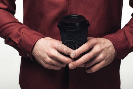 cropped view of man holding black disposable cup isolated on grey