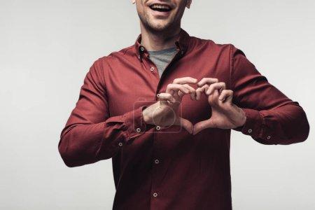 Photo pour Vue partielle de l'homme gai affichant le signe de coeur avec des mains d'isolement sur le concept gris, d'émotion et d'expression humaine - image libre de droit