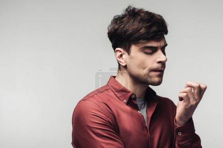Photo pour Bel homme pensif regardant la main isolée sur le gris - image libre de droit