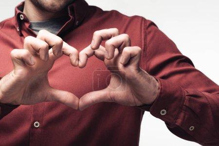 Photo pour Vue partielle de l'homme affichant le signe de coeur avec des mains d'isolement sur le concept gris, d'émotion et d'expression humaine - image libre de droit