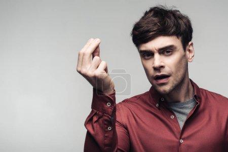 Photo pour Homme insatisfait affichant le geste d'argent et regardant la caméra isolée sur le concept gris, d'émotion humaine et d'expression - image libre de droit