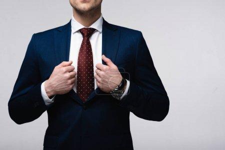 Photo pour Vue recadrée d'homme d'affaires confiant touchant costume isolé sur gris, émotion humaine et concept d'expression - image libre de droit