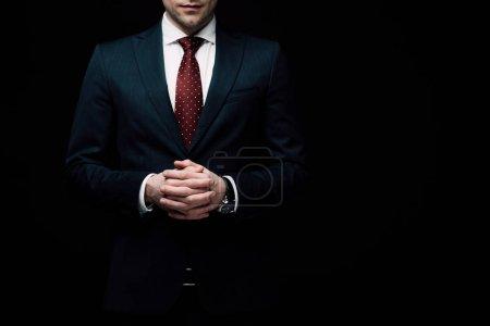 Photo pour Vue partielle de l'homme d'affaires confiant debout avec les mains serrées isolé sur noir, émotion humaine et concept d'expression - image libre de droit