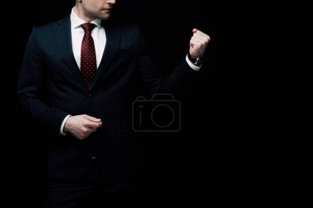 cropped view of angry businessman showing fist isolated on black, human emotion and expression concept