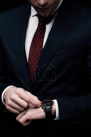 Photo pour Vue recadrée de l'heure de vérification d'homme d'affaires sur la montre isolée sur le noir - image libre de droit