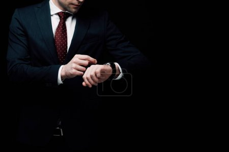 partial view of businessman checking time on watch isolated on black