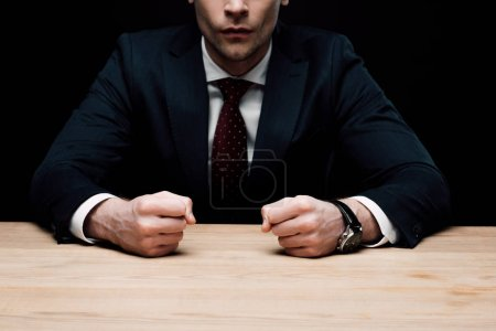 Photo for Partial view of angry businessman sitting at table and holding fists isolated on black, human emotion and expression concept - Royalty Free Image