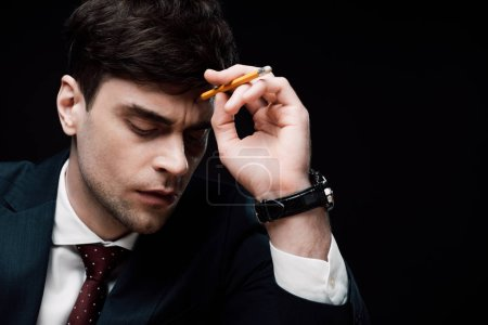 serious businessman with closed eyes touching head with pencil isolated on black