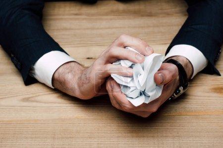 Photo pour Vue partielle de l'homme d'affaires assis à table et papier friable - image libre de droit