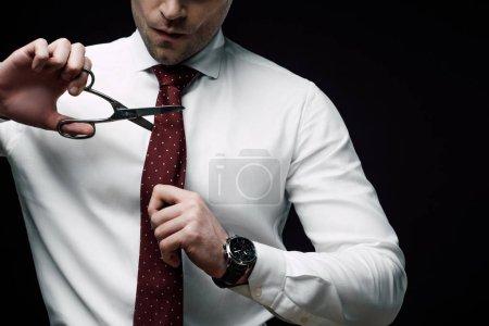 Photo pour Vue recadrée de l'homme d'affaires déçu coupe cravate avec ciseaux isolés sur noir - image libre de droit
