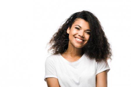 Photo pour Joyeuse fille afro-américaine en t-shirt blanc regardant la caméra isolée sur blanc - image libre de droit