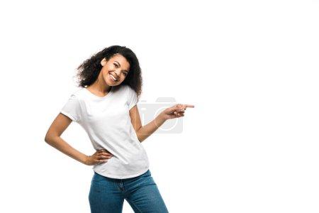 Photo pour Heureuse fille afro-américaine en t-shirt blanc pointant du doigt tout en se tenant avec la main sur la hanche isolé sur blanc - image libre de droit
