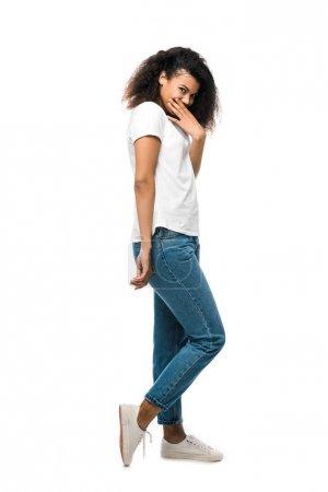 Afrikanerin verdeckt Gesicht mit der Hand und steht in blauen Jeans isoliert auf weißem Grund