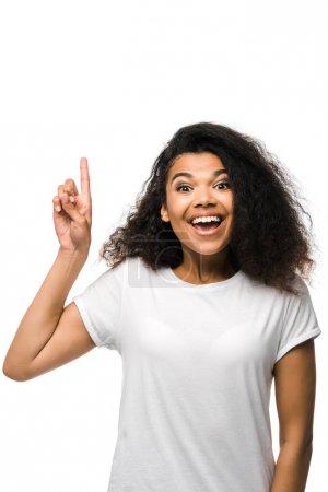 Photo pour Femme afro-américaine souriante en t-shirt blanc pointant du doigt isolé sur blanc - image libre de droit