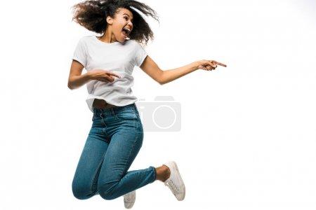 Foto de Alegre mujer afroamericana señalando con los dedos y saltando aislado en blanco - Imagen libre de derechos
