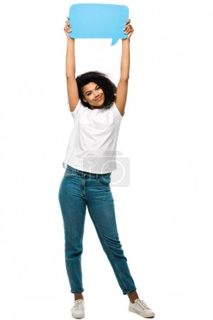 happy african american girl holding blue speech bubble while standing in blue jeans isolated on white